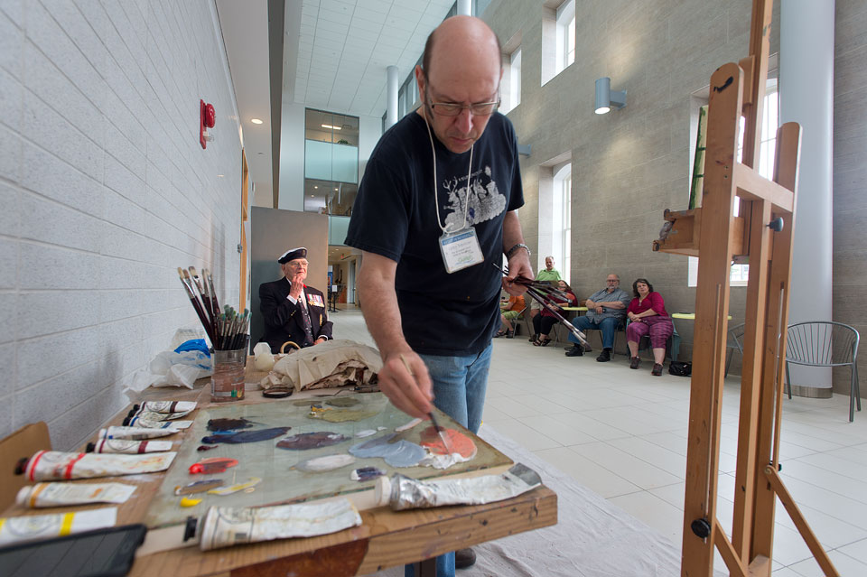 Guelph artist Greg Denton paints a portrait of former U of G president Bill Winegard for Remembrance Day project.