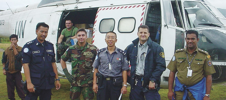 John Remillard standing in front of helicopter with other uniformed men