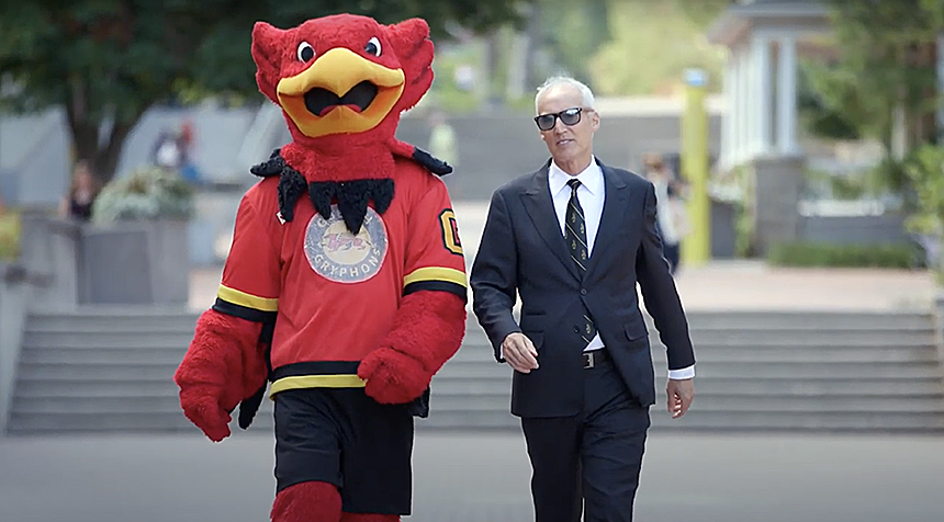 President Dr. Franco J. Vaccarino and University of Guelph mascot Gryph walking
