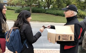 President Dr. Franco J. Vaccarino handing out cookies at the bus stop to students going home