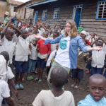 Happy young woman surrounded by African children