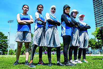 six members of the Hijabi Ballers standing on the field