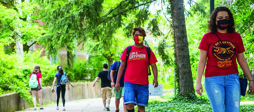 students walking 6 feet apart on campus while wearing masks