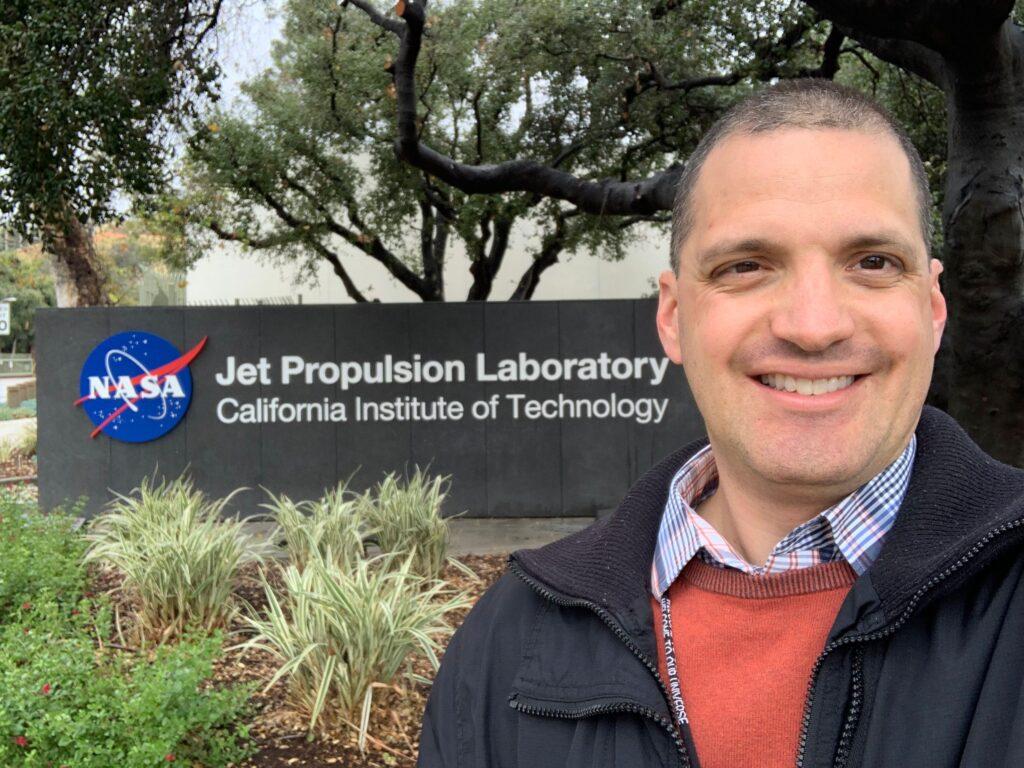 closeup smiling man before sign saying NASA Jet Propulsion Laboratory