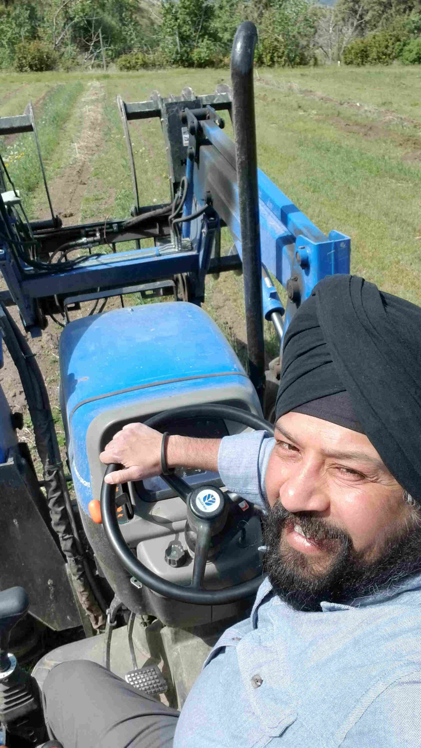 man looking back and smiling aboard tractor