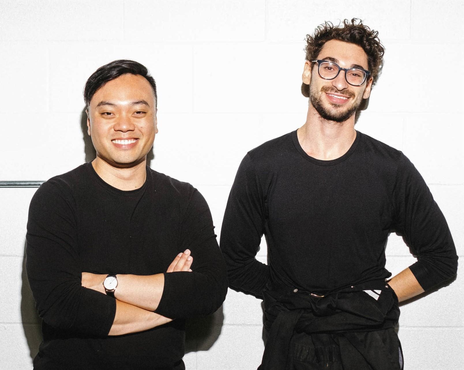 two men in black smile at camera