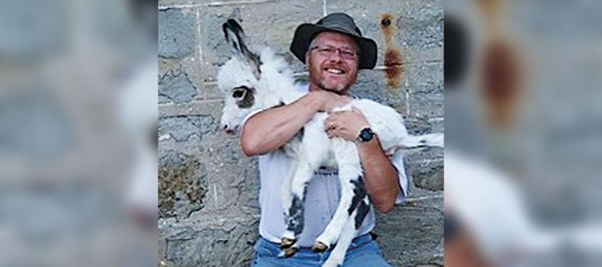 andy robinson holding a miniture donkey